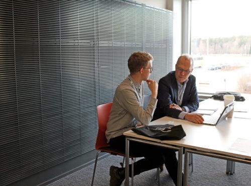 Tekniikan alan opiskelija ja yrityksen edustaja keskustelevat pöydän ääressä.