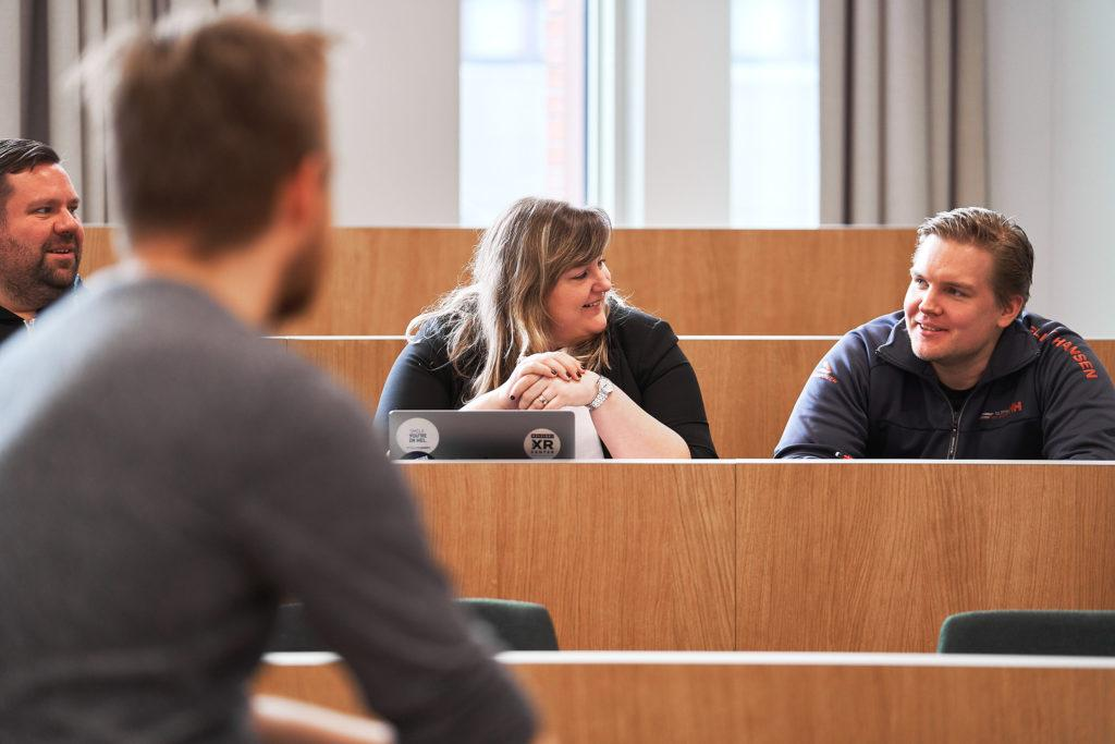 Neljä henkilöä istuvat luokkahuoneessa ja keskustelevat keskenään.